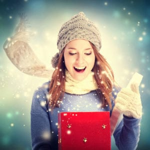 Surprised woman in winter clothes opening a box full of sparkles