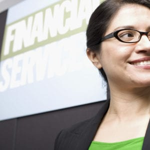"a woman with glasses smiling in front a big banner that says ""financial services"""