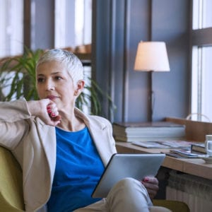 a contemplative older woman with short silver hair clenching her fist and holding a tablet