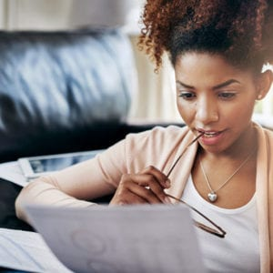 Young woman looking over documents while chewing on her glasses