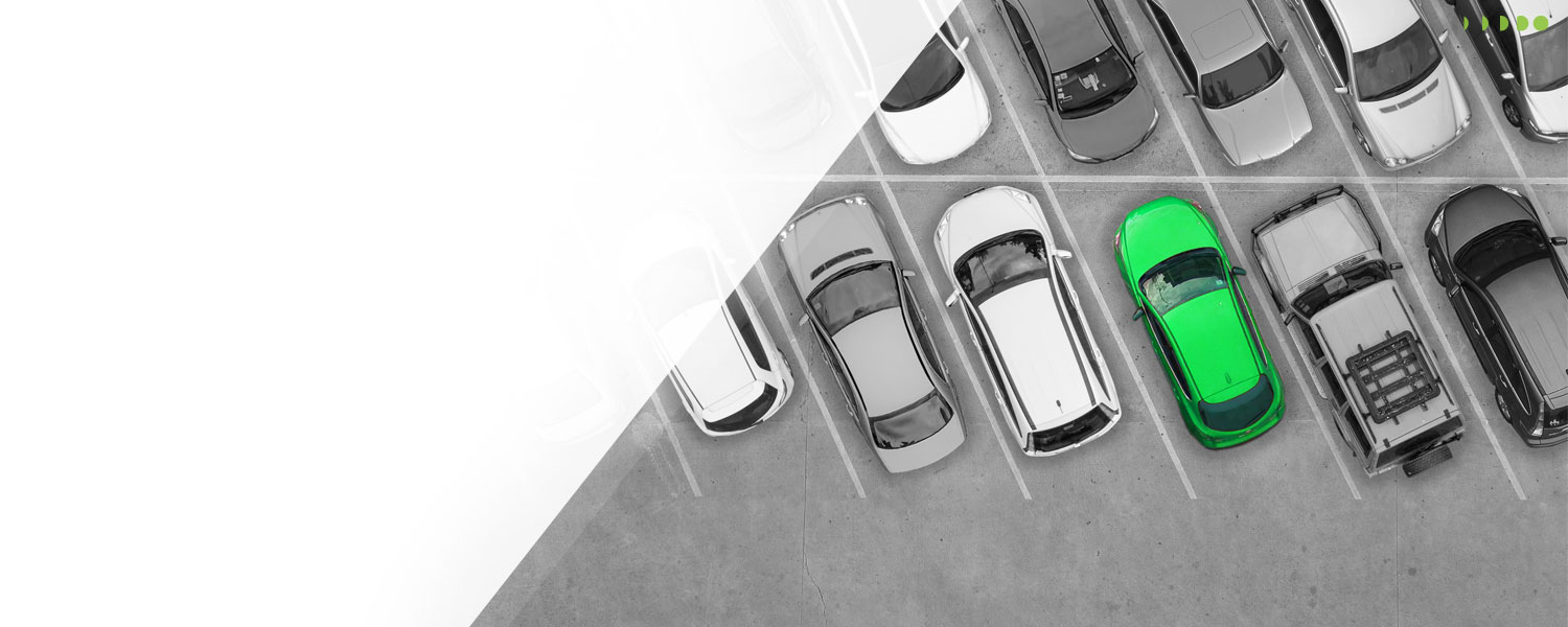 Slier image of parked cars. All of them are black and white except for one that is green to symbolize the car that has the Signal low rate.