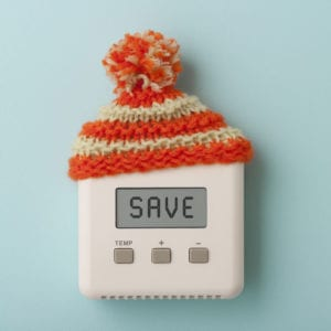 "Thermostat with the word ""SAVE"" on screen and a small winter hat on top."