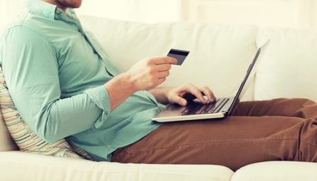 Man on sofa holding credit card