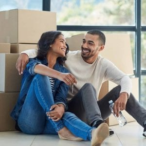 a young couple is taking a break from loading boxes into their new home. They are seated on the floor embracing and gazing into each other's eyes while the woman holds the key to their new home...and probably his heart, too.