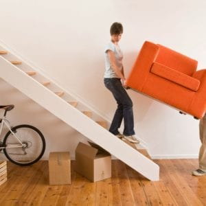 a couple moving a large orange chair into their new home.