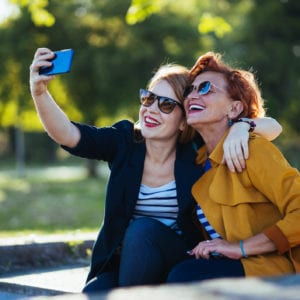 Mother and adult daughter taking photo on cellphone