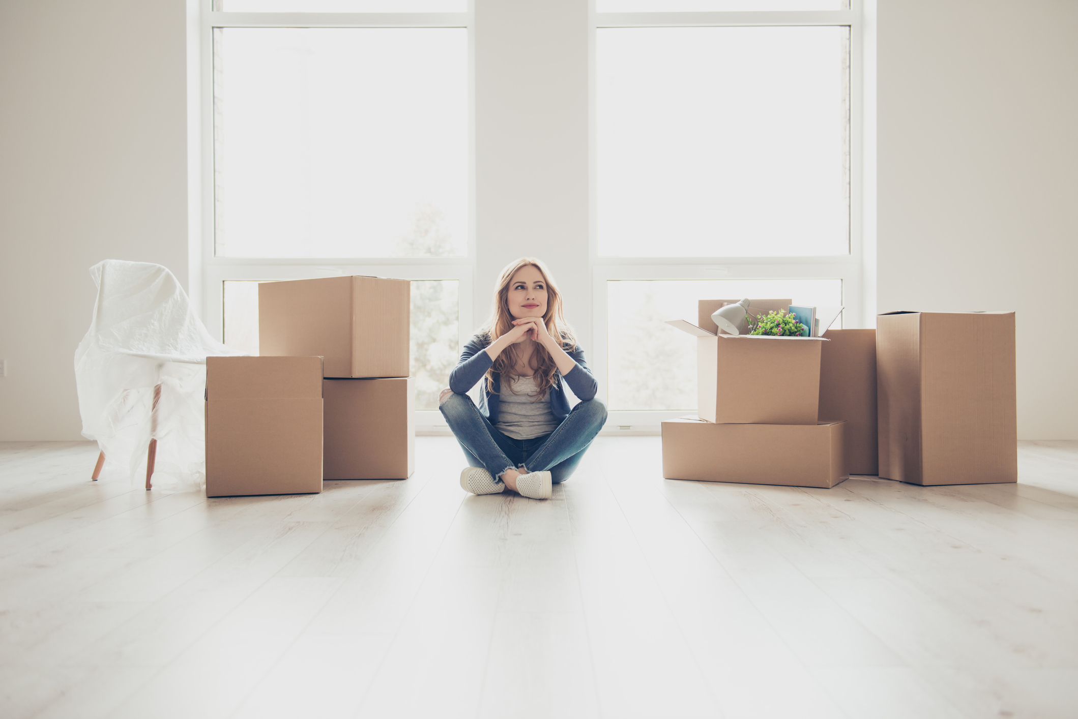 women sitting next to boxes moving