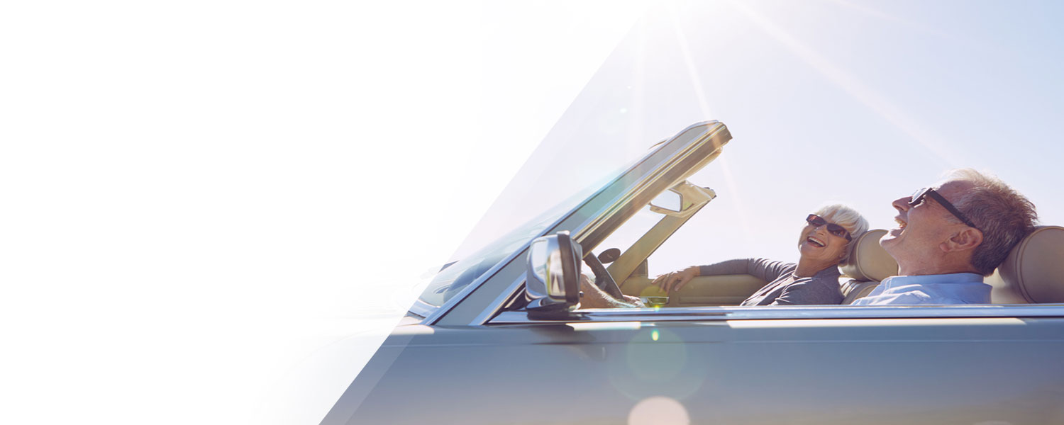 Man and woman riding in convertible