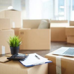 Several unpacked carton boxes with office supplies, laptop, papers, calculator and green plant in flowerpot on top of packages